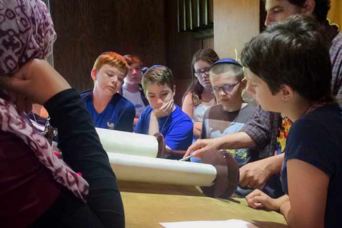 Participants in the Kids4Peace summer day camp look at the Torah at Herzu Ner-Tamid Synagogue on Mercer Island. (Photo by Ahlaam Ibraahim)