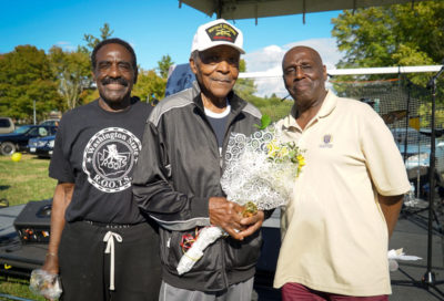 ROOTS Committee members Paul Mitchell and William Lowe present the oldest man at the picnic, 95 year old Clyde Robinson with flowers and a gold trophy.