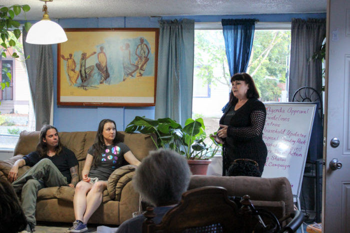 Pina Orsillo Belgrano, right, who fought foreclosure on her own home in Beacon Hill, addresses a meeting of SAFE volunteers in the Slack's living room. (Photo by Alia Marsha)