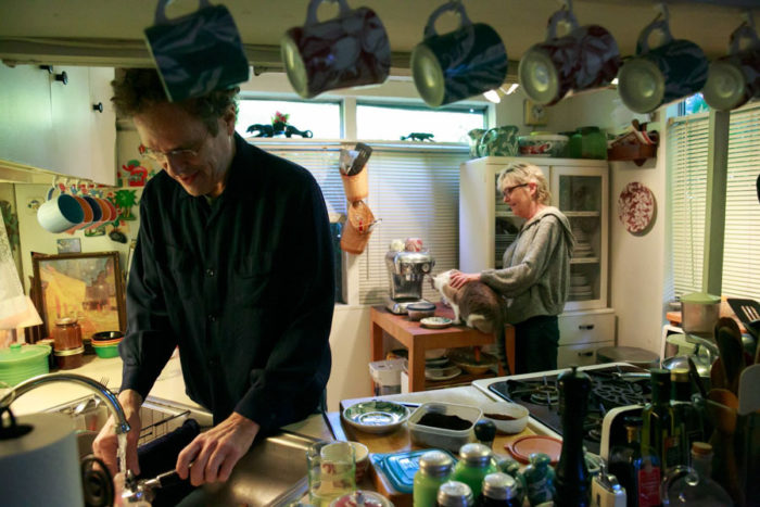Jeff Holtzman and Jill Haas talk in their kitchen at University Trailer Park. They're reluctant to leave the 500- square-foot-home and are looking for a new trailer in Olympia. (Photo by Erika Schultz / The Seattle Times)
