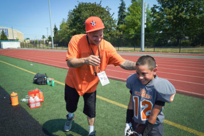 PAC Chargers 89er's coach Dixon Farmer congratulates his son Dixon Jr. after the run.