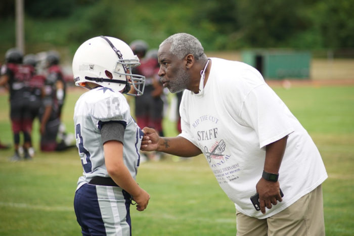 Beacon Hill Cowboy Junior Head Coach Allen Brooks talks with Junior QB Kade Bainbridge.
