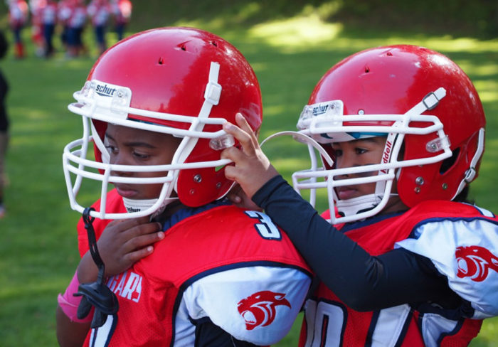 A South West Athletics Club Cougar helps his teammate with his helmet before a 2013 game against the Rainier Eagles.