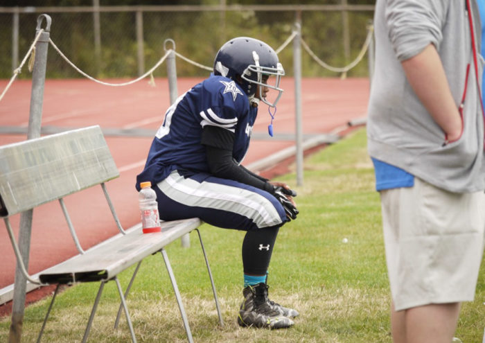 Byron Jones of the Cowboy Juniors waits on the bench before going back out on the field against the Renton Rangers.