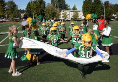 The Lake City team bursts through a banner held by their cheer squad before a game a few years ago.