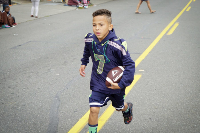 A Seattle Jr. Seahawks player runs to catch up to his teammates during the 2016 Umoja Fest Parade.