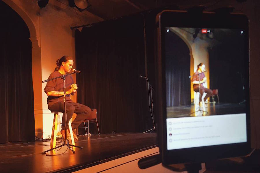 """Artist Roldy Aguero Ablao tells a story at The Seattle Globalist's """"Stories of Finding Home"""" storytelling event. (Photo by Alex Stonehill.)"""