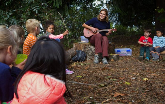 Rachel Franz, lead teacher at Tiny Trees sings to her students. The new outdoor daycare inspired by Scandinavian models claims to provide much more affordable daycare options especially in diverse and low income neighborhoods. (Photo by Ellen Banner / The Seattle Times)