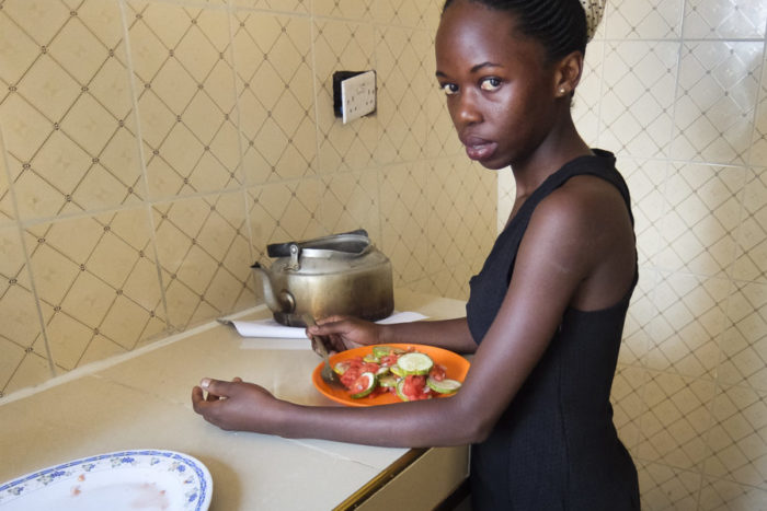 Agness Achan eats vegetables in her kitchen. She is among a growing number of Ugandan girls and women who struggle with eating disorders. (Photo by Edna Namara for GPJ Uganda)