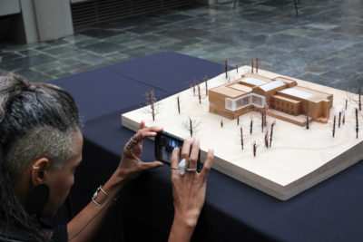 At a community outreach meeting Cayetana San Segundo takes a photo of a model of what the new Seattle Asian Art Museum will look like in 2019. (Photo by Alia Marsha)