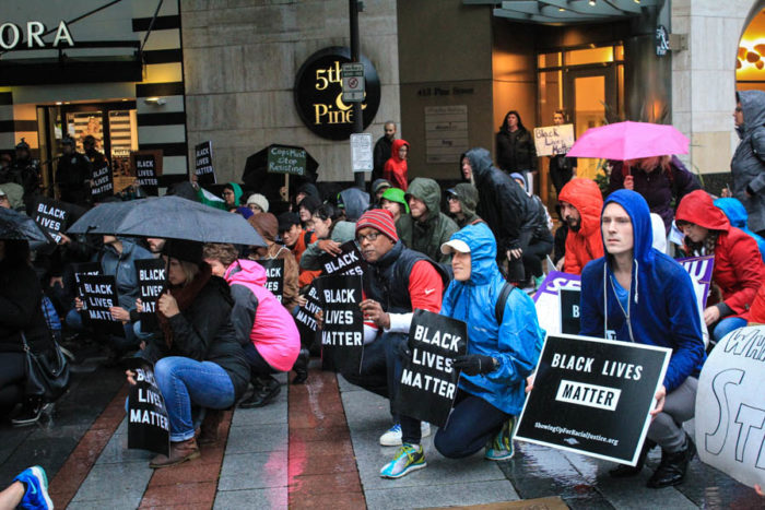 Protesters at Westlake Park start the rally and march by kneeling for the national anthem. (Photo by Melissa Lin.)
