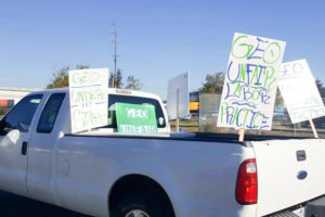 "Employee cars and trucks parked outside of the Northwest Detention Center yesterday had picket signs charging ""unfair labor practices"" and understaffing"" at the privately-run facility. (Photo by Victoria Mena)"