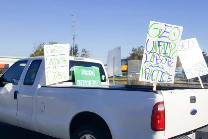 "Employee cars and trucks parked outside of the Northwest Detention Center on Tuesday had picket signs charging ""unfair labor practices"" and understaffing"" at the privately-run facility. (Photo by Victoria Mena)"