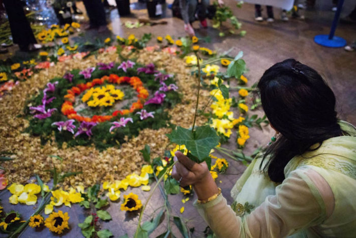 Puja Chauhan helps create flower rangoli art, led by artist Annie Penta, during a Festival of Lights Diwali celebration at the Seattle Center Armory in 2014. (Lindsey Wasson / The Seattle Times)
