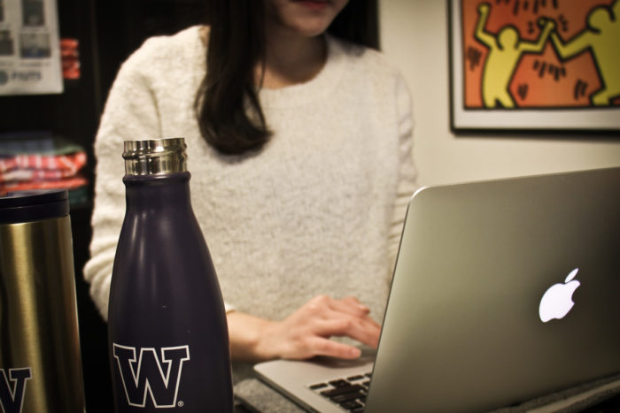 Cecilia Zhong uses a computer at FIUTS, a nonprofit that helps international students adjust to life at UW — and avoid becoming targets of scammers. (Photo by Bernard Ellouk)