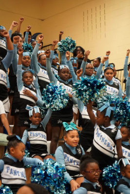 Members of the CD Panthers Cheer Squad stand and raise fists during the national anthem. (Photo by Susan Fried)