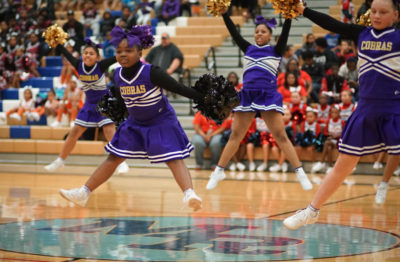 Aniyah 8 (center) and her teammates on the Kent Cobras perform an X jump.