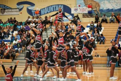 """The Mini Renton Rangers Cheerleaders perform """"the elevator"""" one of the more difficult stunts in cheerleading. (Photo by Susan Fried)"""
