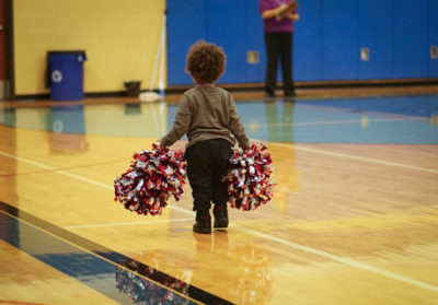 A little boy helps pick up pompoms after the Renton Rangers competition-winning performance. (Photo by Susan Fried)