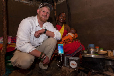 Ryan Ahearn with a JikoPower user in Kenya. The spark's copper prong is placed in a cook fire then heat is transferred to a cup filled with water, sends power to the usb charging port. (Courtesy photo)
