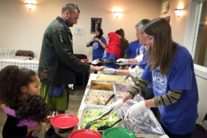 Volunteers serve food at last year's interfaith Christmas Eve Dinner. (Photo courtesy Muslim Community Resource Center)