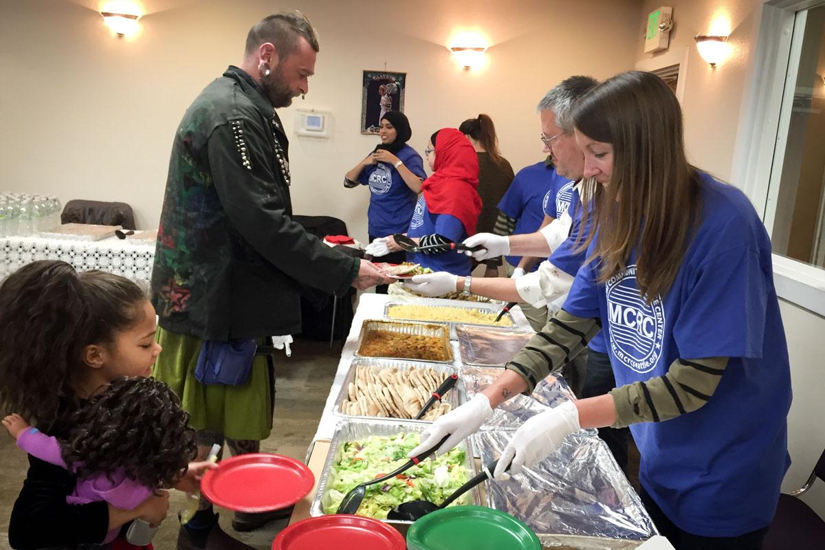 Volunteers serve food at last year's interfaith Christmas Eve Dinner. (Photo courtesy Muslim Community Resource Center)