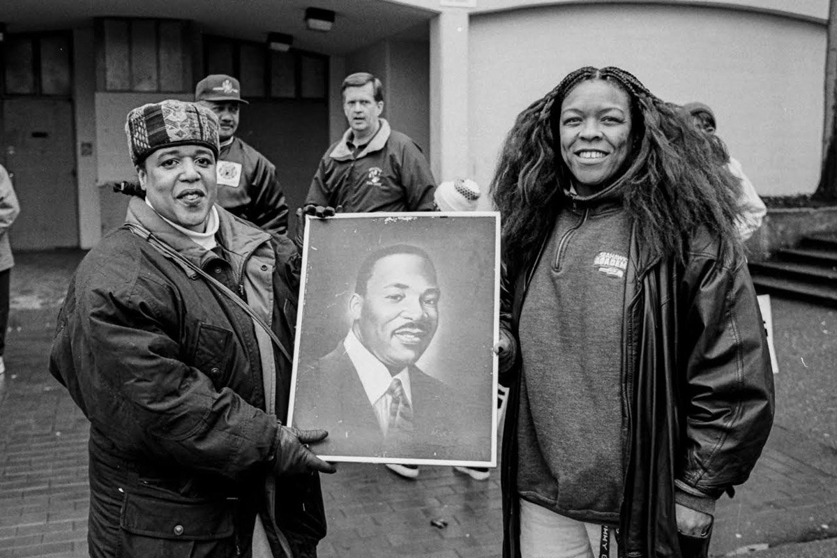 Fai Mathews, left, has been at most every MLK Day Celebration for the last two decades, always carrying the same picture of Dr. King. (Photo by Susan Fried)