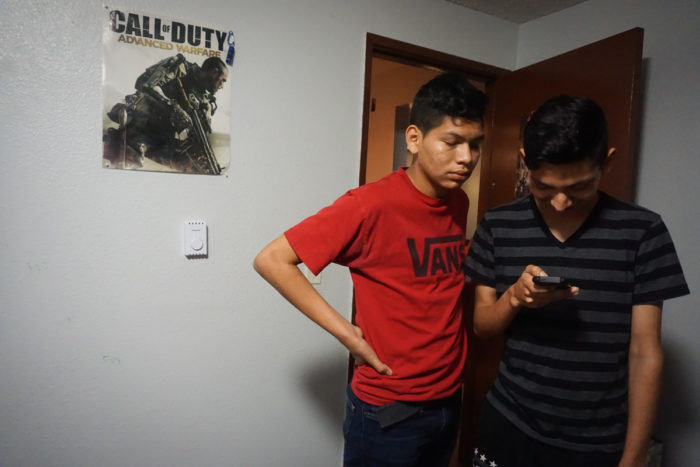 Ricardo, at right, looks at something on his phone while his brother watches alongside him. (Photo by Agatha Pacheco)