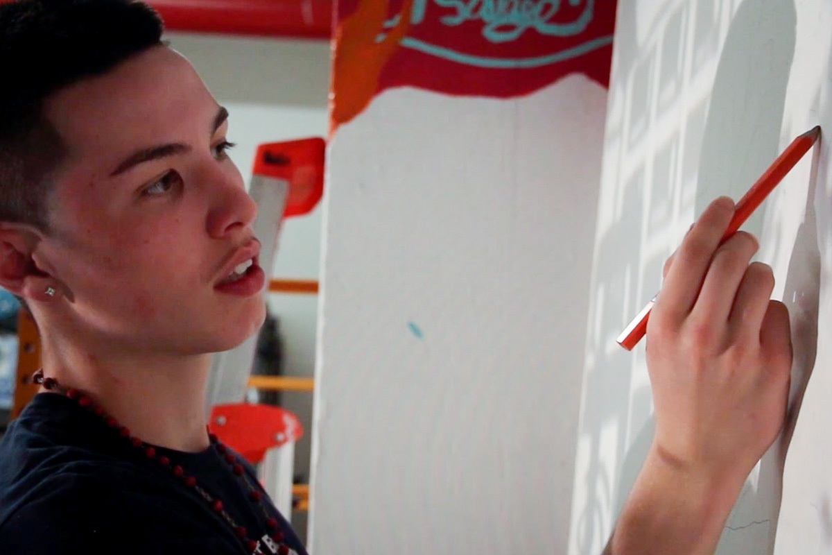 Finn Sullivan works on a mural panel at Urban ArtWorks. (Video still by Kenndy Wirth)