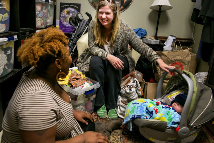 Suzanne Brewer Melchor, center, and her son Mateo, are greeted by outreach birth doula Rokea Jones in the baby boutique room at Open Arms Perinatal Services. (Photo by Johnny Andrews / The Seattle Times)