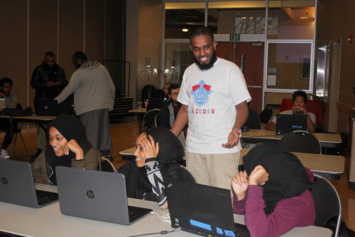 Volunteer Mukhtar Sharif helps Jemila Abdullah, Iftin Kedir and Munera Mohammed (from left) during a coding class for East African youth held by Companion Athletics. (Photo by Goorish Wibneh)