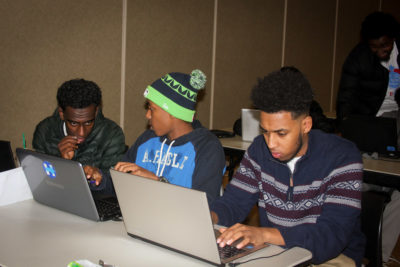 Awol Ibrahim (center) and Dursa Mohammed (right) bridged from Companion Athletics sports programs into the coding classes. (Photo by Goorish Wibneh)