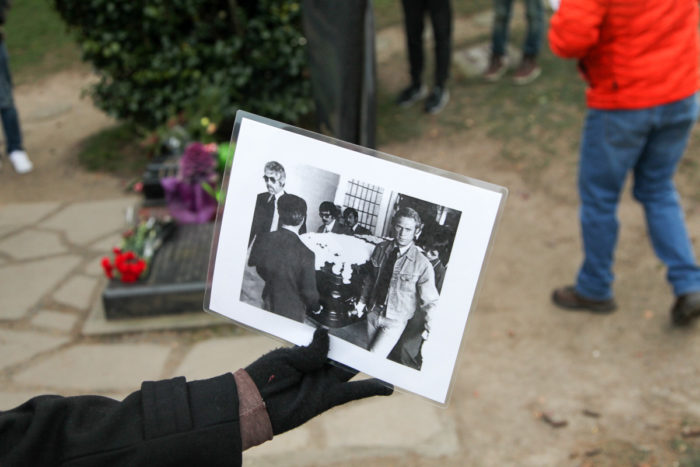A participant in the Lake View Cemetery tour holds a photo of Steve McQueen (sporting Canadian Tuxedo) as a pallbearer at Bruce Lee's funeral. Lee and his son Brandon's grave sites draw visitors from around the world. (Photo by Alex Stonehill)