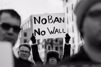 A protester holds a sign during a rally against President Donald Trump's initial travel ban in January. (Photo by Lorie Shaull via Flickr)