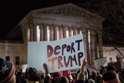A crowd protests President Donald Trump's first travel ban in January (Photo by Lorie Shaull via Flickr)