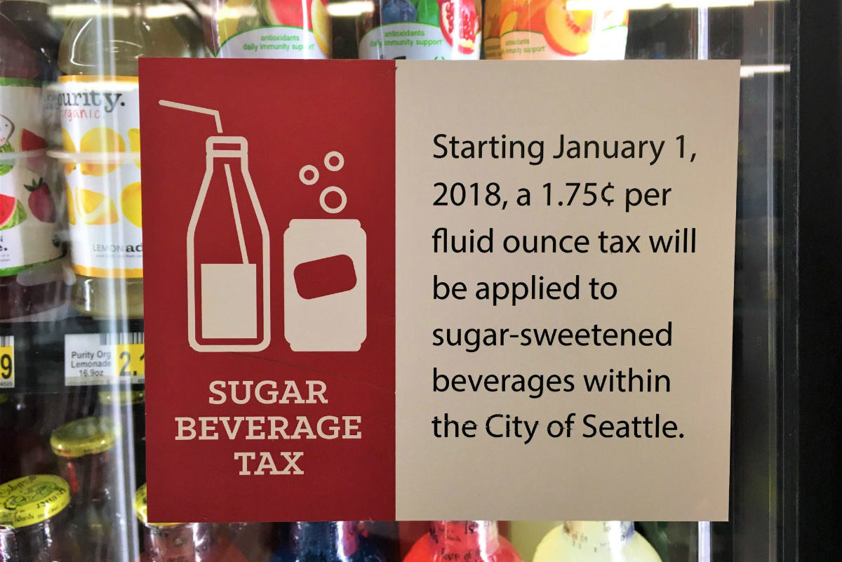"A sign inside the glass of a Seattle drugstore drink cooler informs customers of the new ""Soda Tax."" A classic 20 ounce bottle of Coca Cola might be priced at $2.00 but cost $2.35 due to the cola's sugar content. (Photo by Mikaela Lobe)"