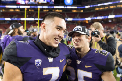 Taylor Rapp (left) celebrates winning the Pac-12 championship with Sean McGrew (right) after Washington defeated Utah 10-3. Rapp is entering the NFL Draft this year, and will hope to be the first Chinese American selected since 2010. Photo Credit: Conor Courtney