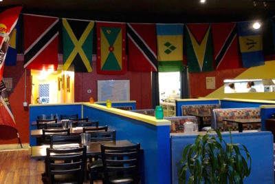 Caribbean flags adorn the colorful walls inside Pam's Kitchen in Wallingford, Seattle. Pamela Jacob, owner and cook at Pam's Kitchen is originally from Trinidad, but moved to Seattle in 1994 to stay with family. (Photo by Alexandra Polk)