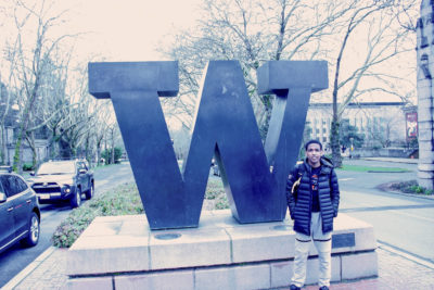 "Tibebu Proctor stands in front of the giant ""W"" at the North end of the University of Washington campus. When choosing which college where he would run, he chose Washington over Wake Forest, because of Washington's proximity to home. (Photo by Andy Yamashita)"